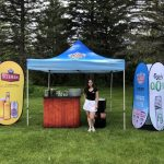 (Fr) Brand ambassador standing next to booth, complete with a Sleeman pop-up tent, sampling counter and two Flexi Signs.