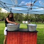 Brand ambassador standing next to sampling counter with 2 ice buckets.